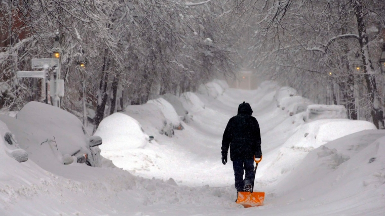A man drags a shovel up Beacon Hill during a severe winter snow storm in Boston